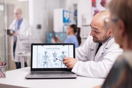 Doctor explaning back pain to senior patient in hospital office pointing at laptop screen with human skeleton. Nurse in blue uniform holding radiography and elderly doctor taking notes on clipboard in clinic corridor.