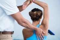 Physiotherapist giving shoulder therapy to a woman in clinic